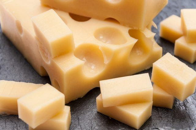 Emmental cheese on a gray wooden table.