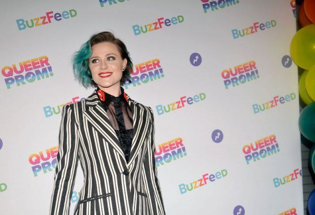 Evan Rachel Woods smiles in a black and white stripped jacket.