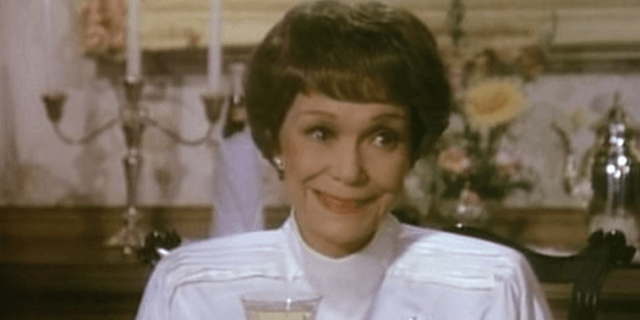 Jane holds a wine glass as she smiles while at the table.