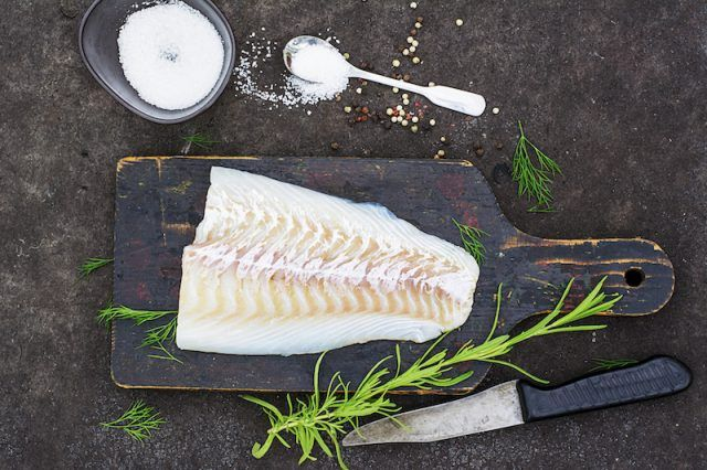 A fish fillet with a knife, salt, and wooden board.