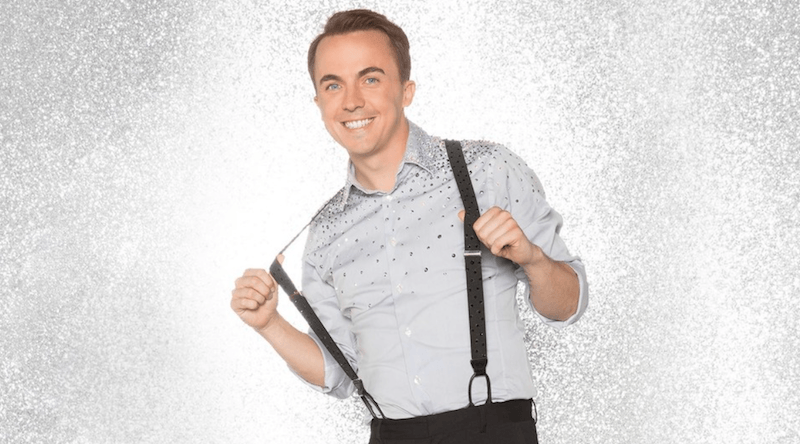 Frankie Muniz holds his suspenders and smiles