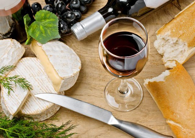 Red wine, cheese, bread and a knife on a wooden table.