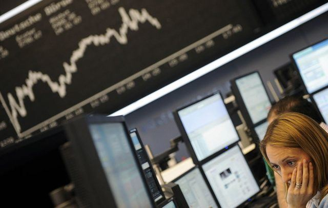 A stock broker sits in front of a board displaying German share index DAX