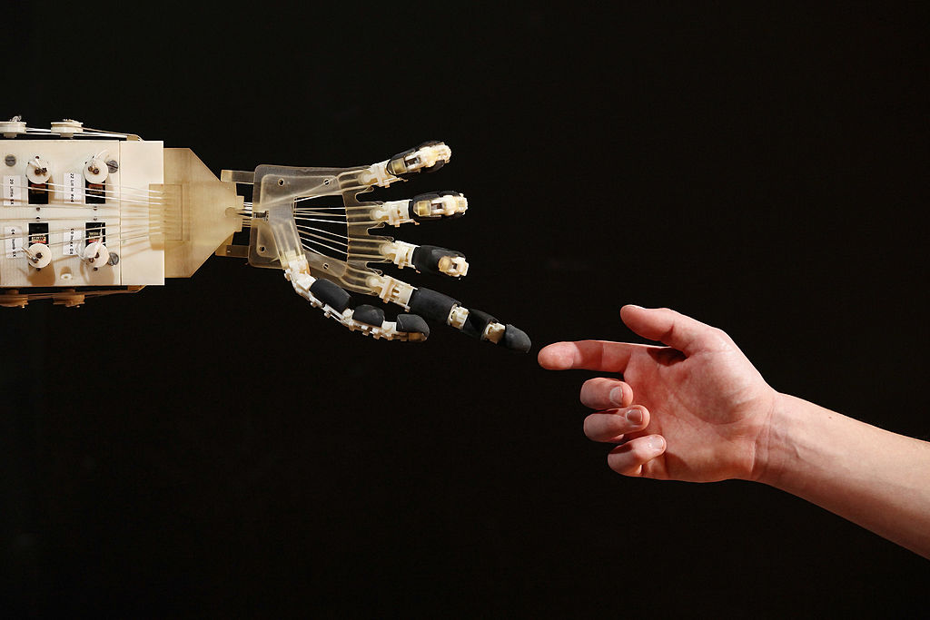 Robot hand extends index finger towards a human index finger