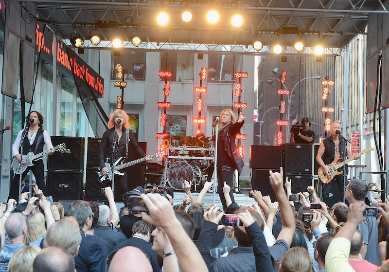Def Leppard performs on stage at an outdoor concert