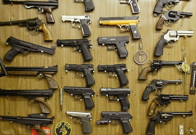 Rows of guns on a wall.