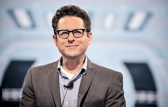 J.J. Abrams sitting in a gray suit and blue tie as he looks outwards towards an audience.