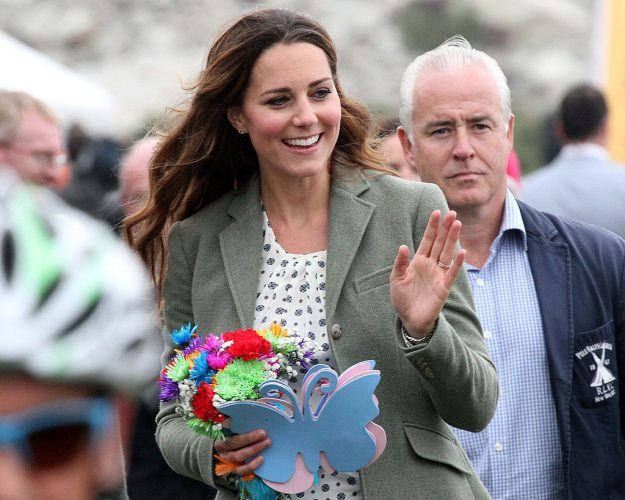 Kate Middleton at marathon holding flowers and gifts.