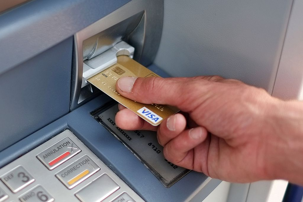 A man takes out banknotes from an automated teller machine (ATM)