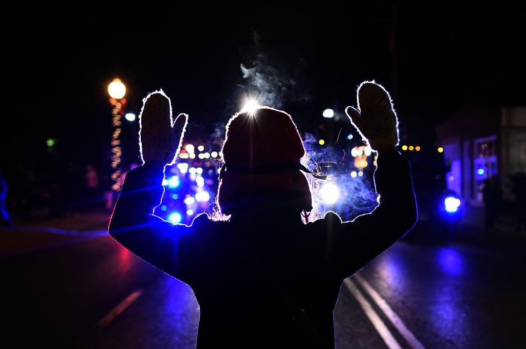 A woman holds her hands up in front of a police car