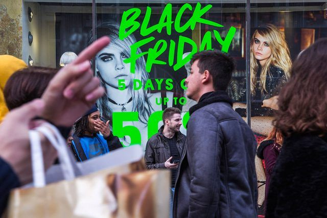 People walk past a shopfront on Oxford Street advertising 'Black Friday' discounts