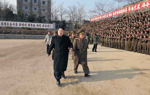 Kim Jong-un walking past his army with a team behind him.