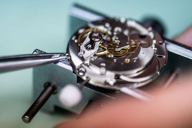 A student works on the mechanism of a wristwatch as he attends a class at the secondary school Mare de Deu de la Merce