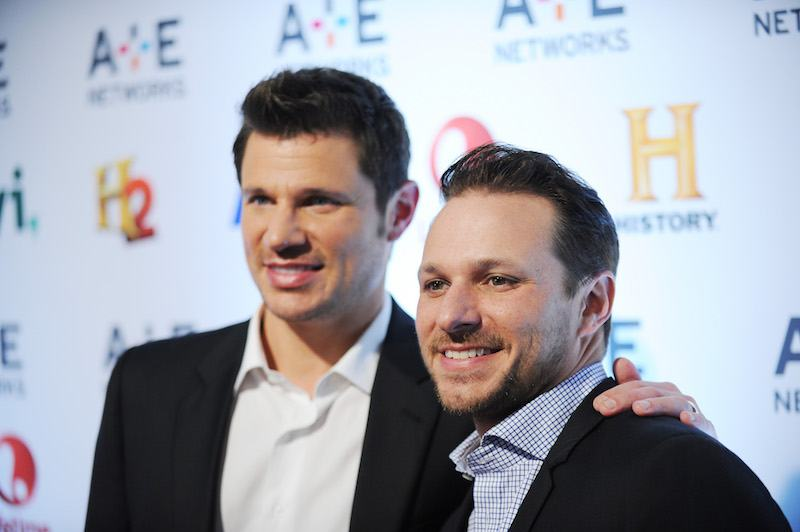 Nick Lachey and Drew Lachey stand next to each other in suits