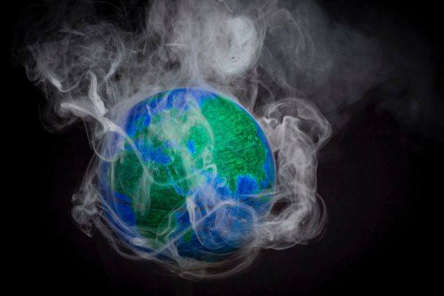 A picture taken on November 10, 2015 shows a small globe surrounded by smoke to illustrate global warming.