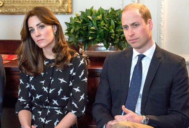 Kate Middleton and Prince William sit in chairs looking somberly forward.