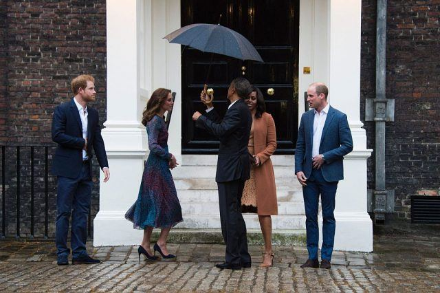 US President Barack Obama (C) holds an umbrella over US First Lady Michelle Obama (2R) as they are greeted by Britain's Prince William, Duke of Cambridge (R), his wife Catherine, Duchess of Cambridge (2R) and Britain's Prince Harry (L) at Kensington Palace in London