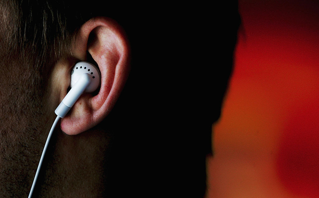 A man listens to an iPod MP3 player through earphones