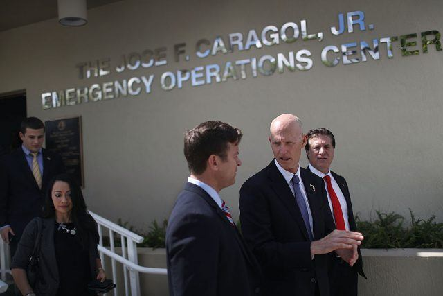 Florida Governor Rick Scott walks with other politicians as he stops by the Jose F. Caragol Jr. Emergency Operations Center on the first day of Hurricane season on June 1, 2016