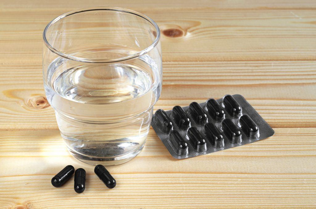 Medical capsules with activated charcoal and glass of water on wooden table