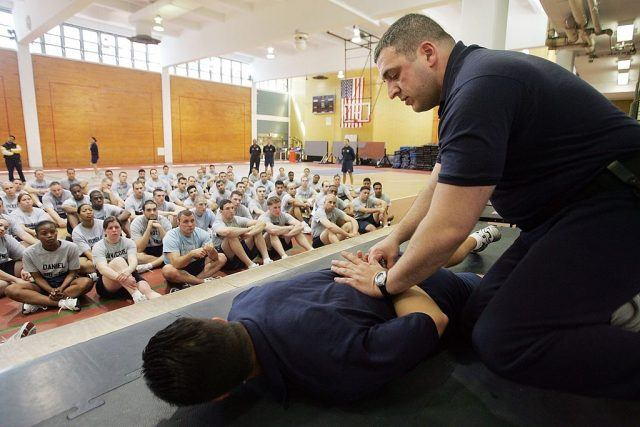 Police officer Billy Pepitone demonstrates handcuffing techniques to recruits at the New York City Police Academy