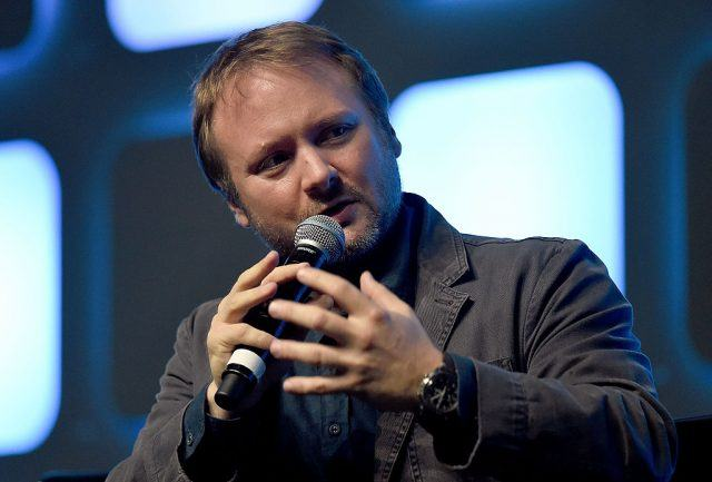 Rian Johnson speaking into a microphone while looking forward at an audience.