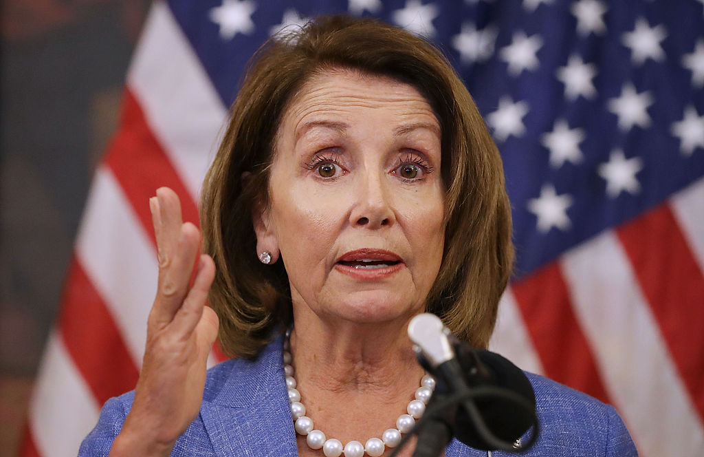 nancy pelosi giving a speech in front of an American flag