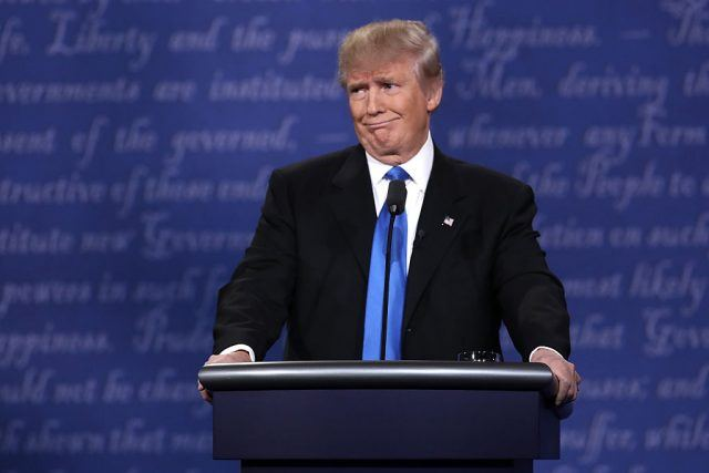 Donald Trump speaking at a podium in a blue tie.