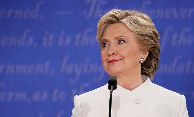 Hillary Clinton stands at a podium wearing a white pantsuit.