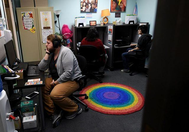 Crisis Service Coordinator Chris Bright (L) looks at a computer monitor with volunteers at the Trevor Project Call Center in West Hollywood, California