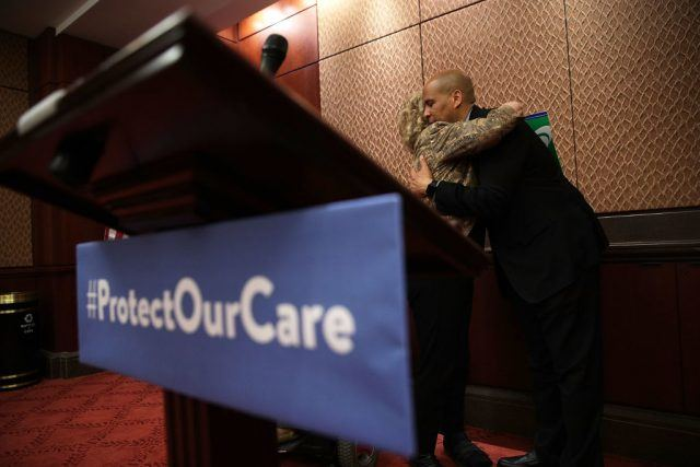 U.S. Sen. Cory Booker (D-NJ) hugs retired social worker Patricia Byrd of Panama City, Florida, whose 92-year-old mother is on Medicaid