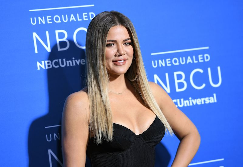 Khloe Kardashian poses with her hand on a hip in a black outfit