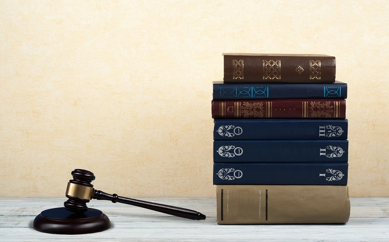 Law concept open book with wooden judges gavel on table in a courtroom or law enforcement office, blue background.