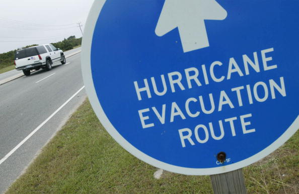 """An SUV Drives by a sign that states """"Evacuation Route"""""""
