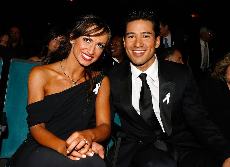 Karina Smirnoff and Mario Lopez sit next to each other in formal wear