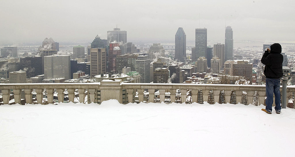 A man takes a picture of the Montreal skyline from the top of Mount Royal