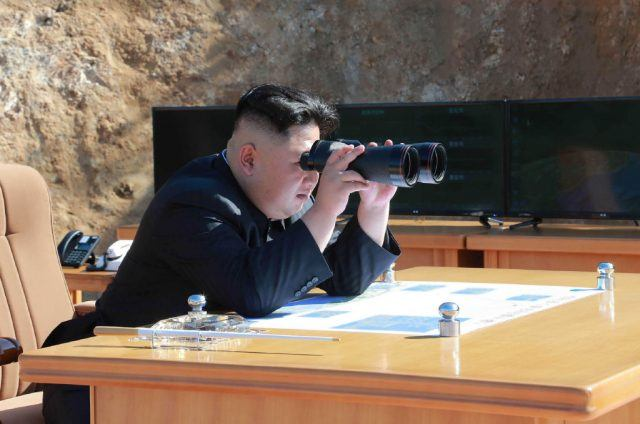 Kim Jong-un looking through binoculars while sitting at a desk.