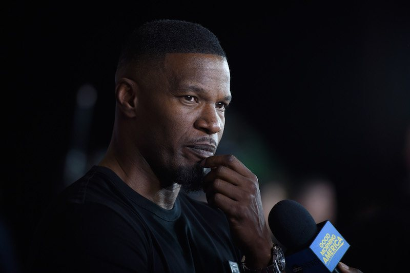 Actor Jamie Foxx holds his hand to his chin while a microphone is held to his face