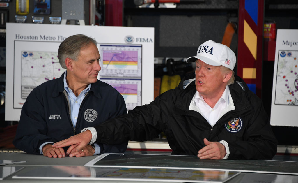 US President Donald Trump (R) sits with Texas Governor Greg Abbott during a briefing on Hurricane Harvey in Corpus Christi, Texas