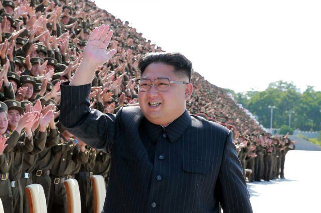 Kim Jong Un waving at a crowd of military soldiers.