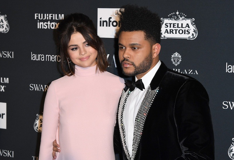 Selena Gomez and The Weeknd pose at an event