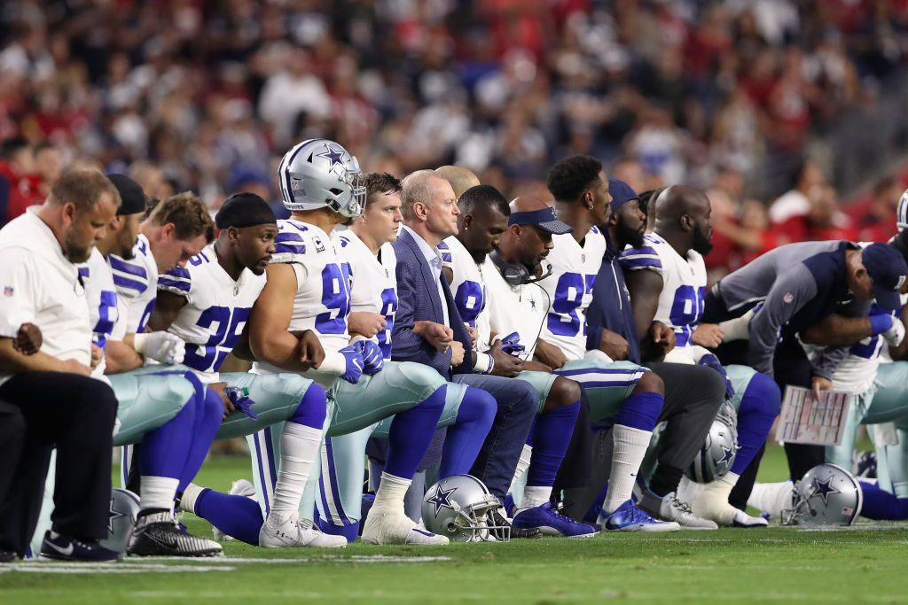 The Dallas Cowboys link arms before the National Anthem at the start of the NFL game against the Arizona Cardinals at the University of Phoenix Stadium on September 25, 2017 in Glendale, Arizona.