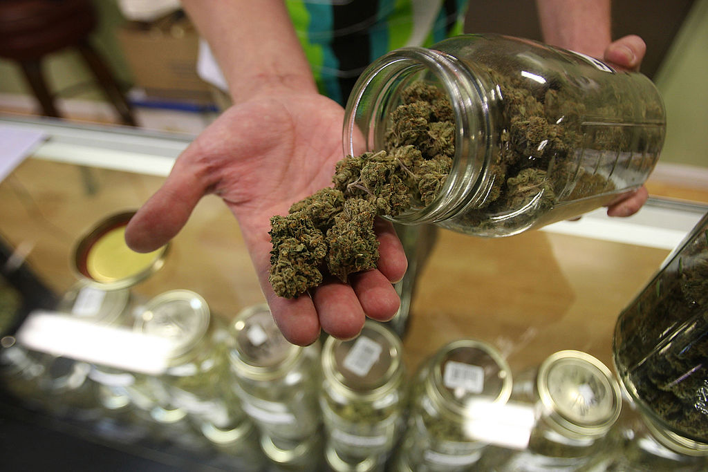 Dave Warden, a bud tender at Private Organic Therapy (P.O.T.), a non-profit co-operative medical marijuana dispensary, displays various types of marijuana available to patients