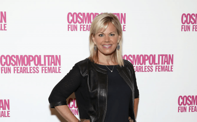 Gretchen Carlson poses with both hands on her hips on a red carpet event.
