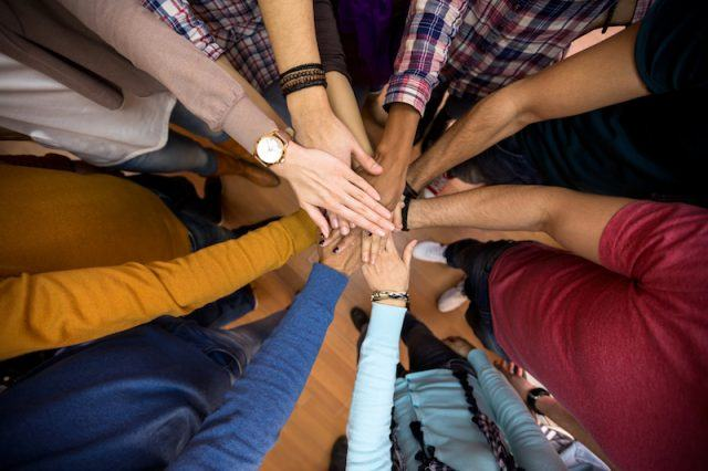 Group of people putting their hands in a huddle