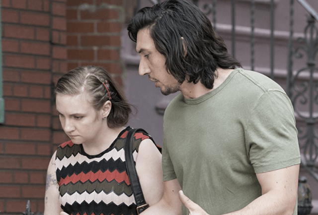 Hannah and Adam walk down a street together while talking.