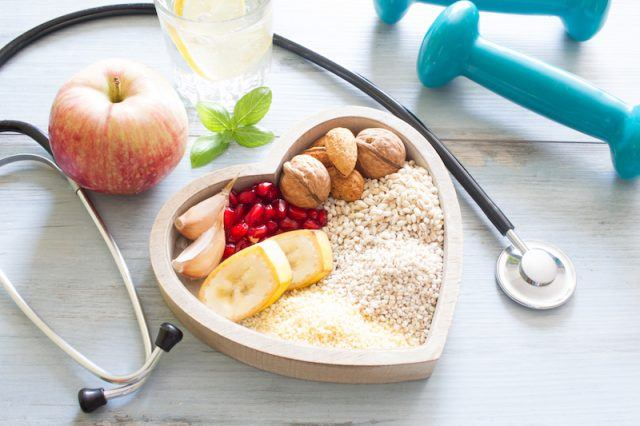 A heart shaped plate with heart-healthy foods and equipment on a white table.