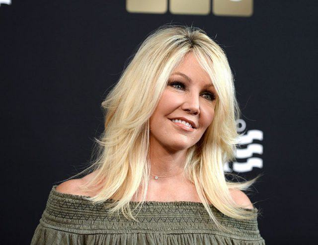 Heather Locklear wears a green dress and smiles at a camera.
