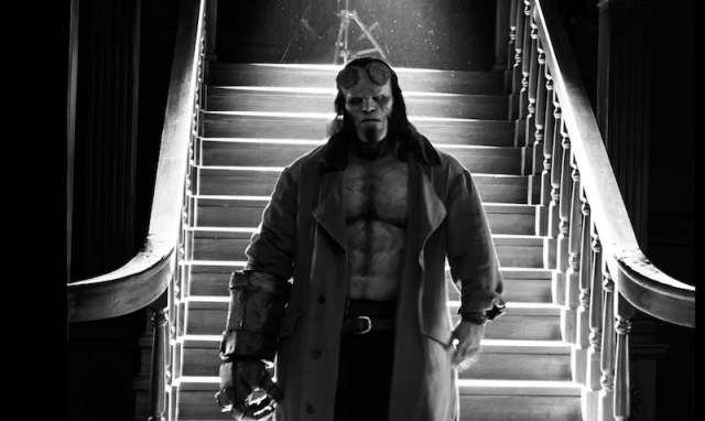 Hellboy stands in front of a long staircase.