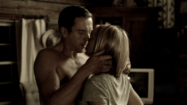 Carrie and Brody kiss inside a bedroom.